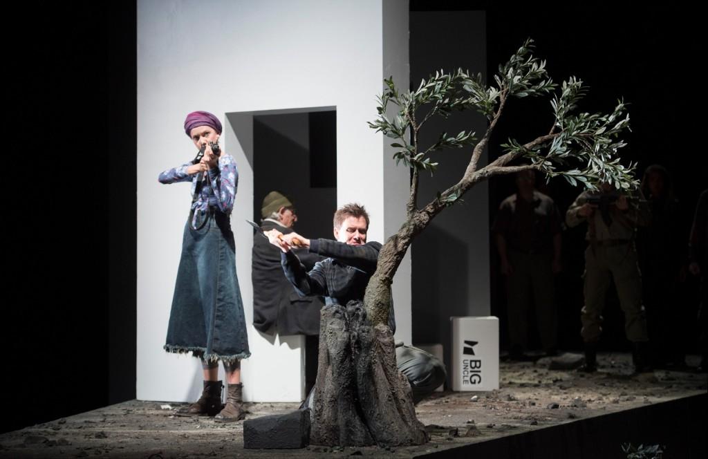 """Chicken-Heart (Alexander Mayr) fällt einen Baum, während seine Frau Sinya (Stine Marie Fischer) bereit ist, abzudrücken, """"An unserem Fluss"""" von Lior Navok an der Oper Frankfurt, Foto: Monika Rittershaus"""