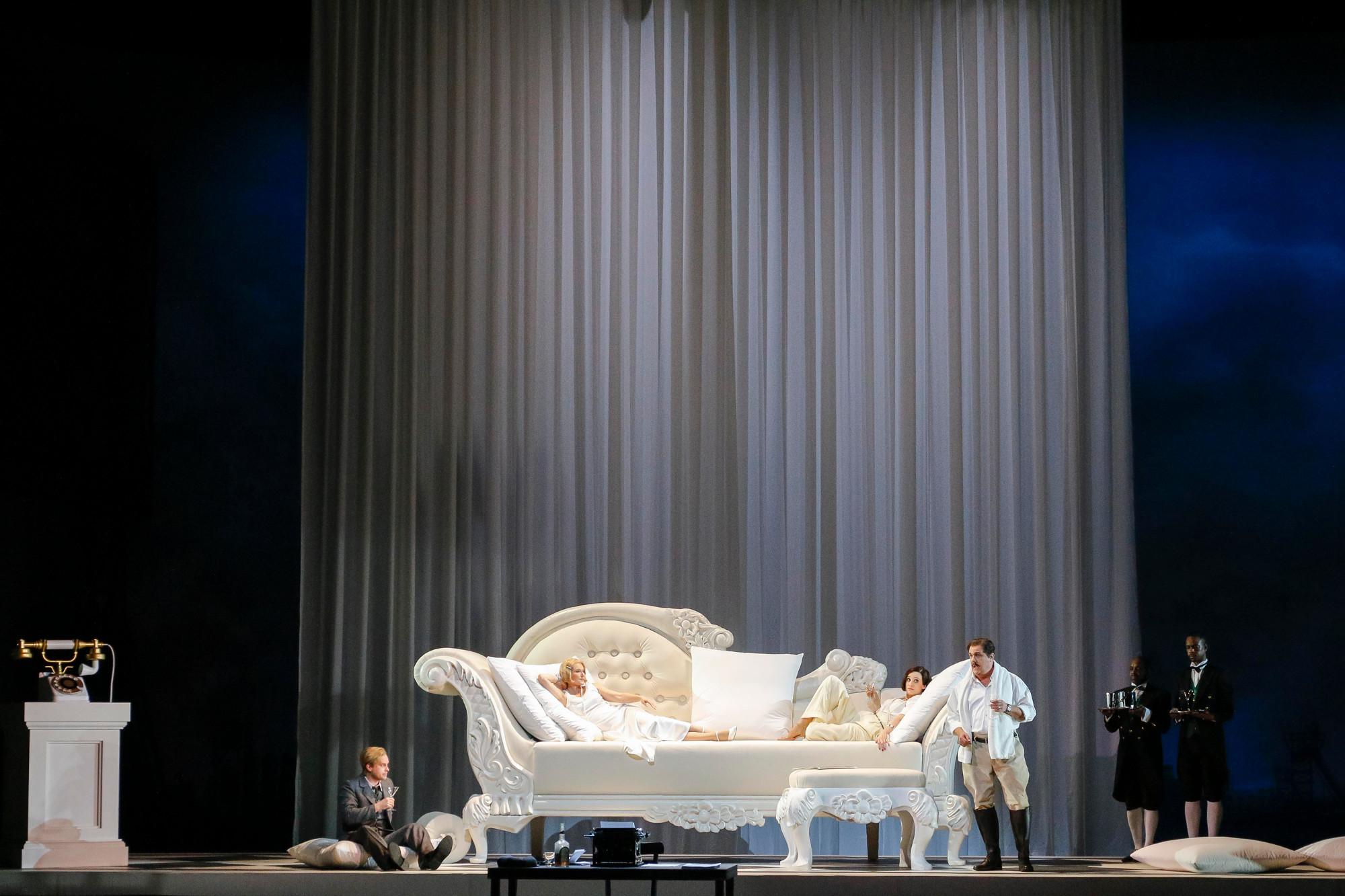 """Während sich Daisy (Maria Bengtsson) und Jordan (Christina Bock) auf der zu groß geratenen Couch räkeln, müssen die Herren Nick (John Chest) und Tom (Raymond Very) es sich daneben gemütlich machen, """"The Great Gatsby"""" von John Harbison an der Semperoper Dresden, Foto: Daniel Koch"""